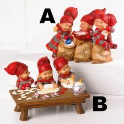 figur med tre babynisser ved et bord som former småkager til jul