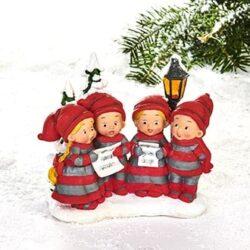 4 Babyelfen hintereinander singen Weihnachtslieder im Chor an der Straßenlaterne